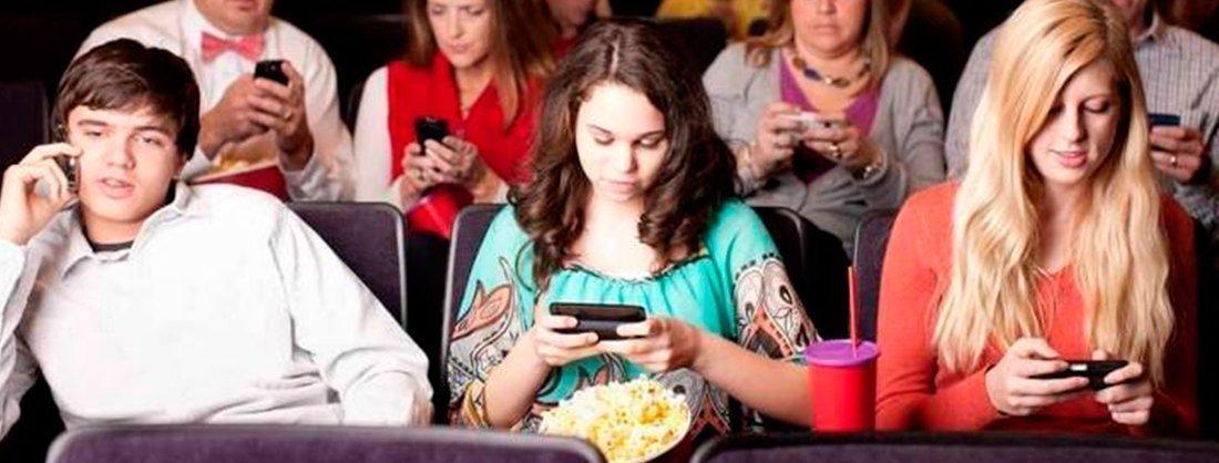 Personas usando el móvil en el cine